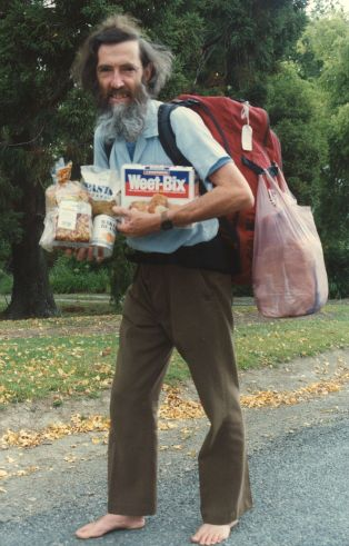[colour photo, David MacClement on road: long dark hair, long beard, red backpack, bare feet]